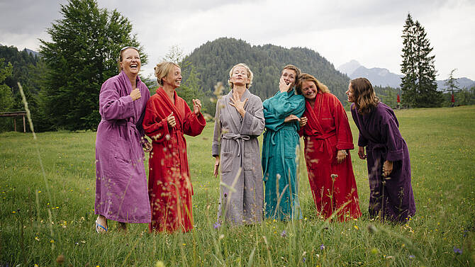 Six women with bathrobes on a meadow celebrating a Girls only Top package